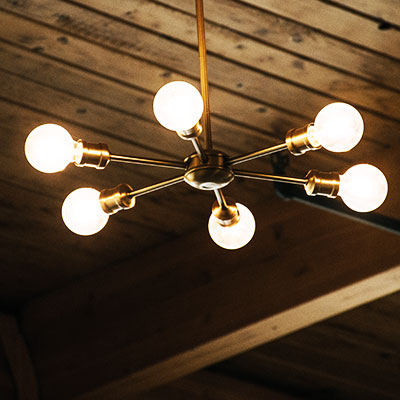 industrial light fixture with LED bulbs on wood paneled ceiling
